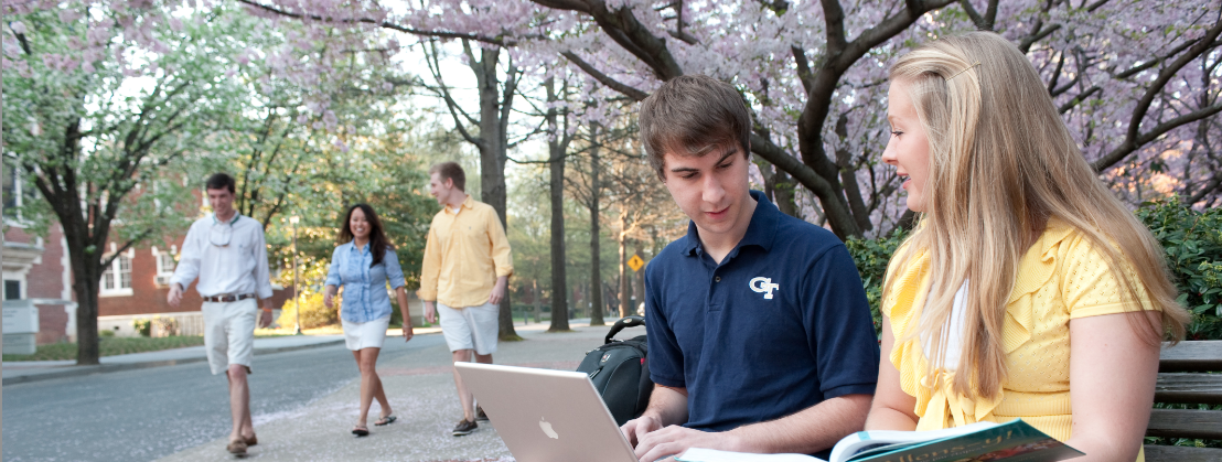 two students talking on a bench with laptops